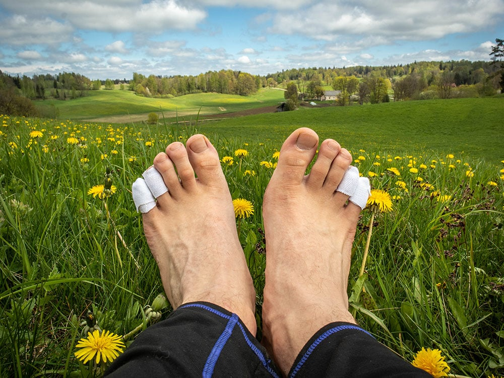 A man with taped bare feet while hiking
