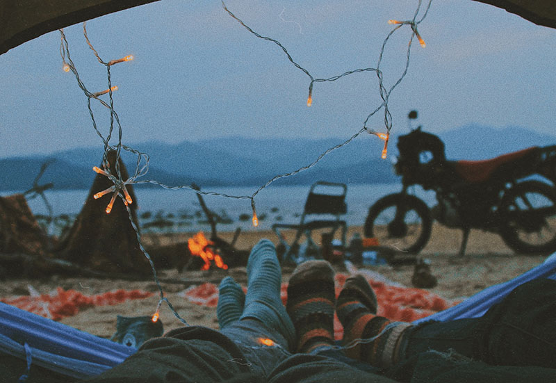 A couple chilling in a tent wearing socks