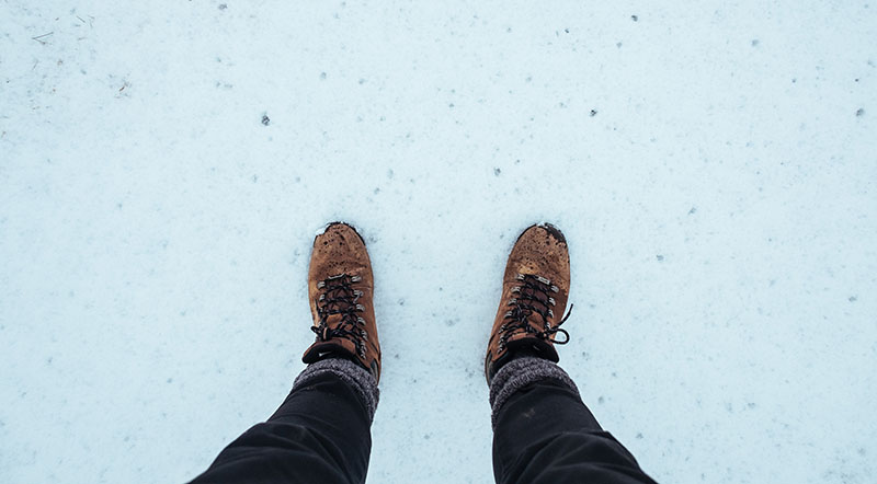 A hiker wearing two pairs of socks and hiking boots in winter