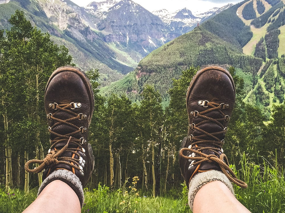 A hiker sitting in the mountains wearing hiking boots and two pairs of socks