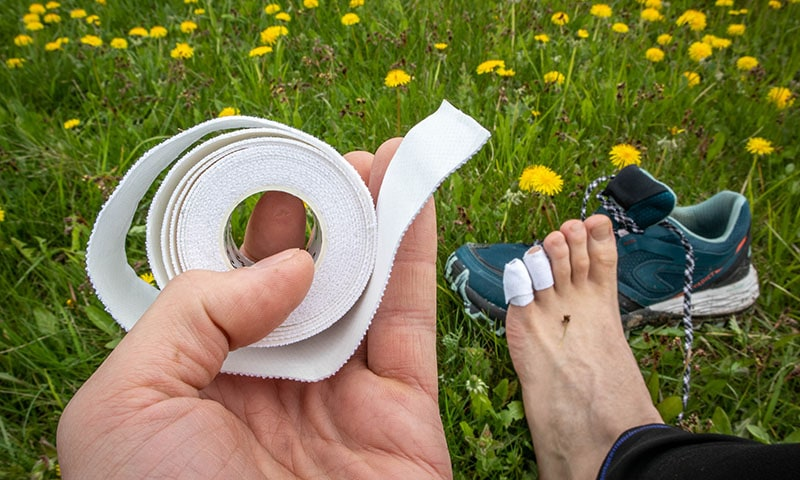 A person holding leukotape in hands with taped feet and hiking shoes in background